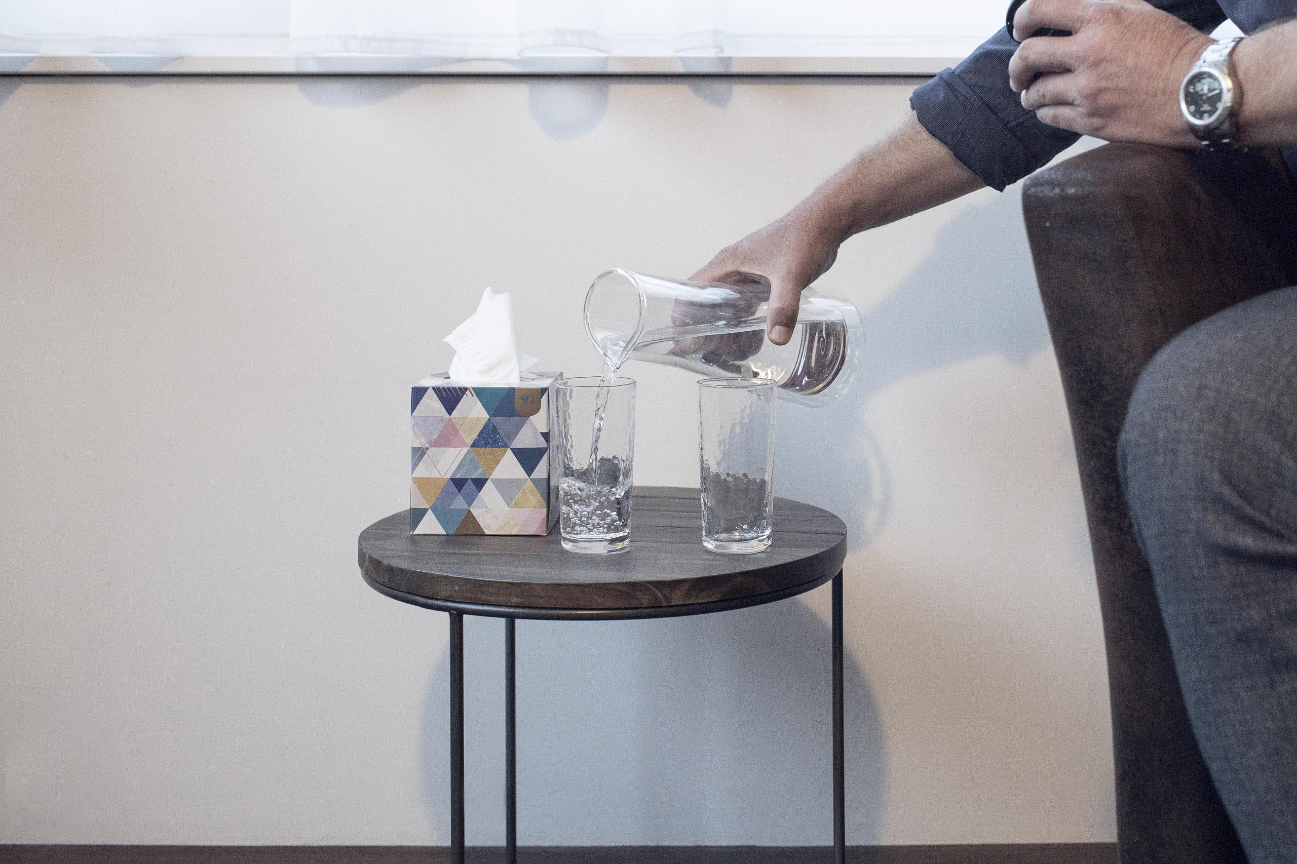 Trinkgläser werden aus einem Krug mit Wasser gefüllt